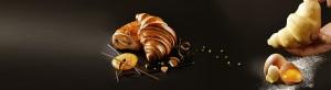 Croissant et pain au chocolat doré avec un zeste de chocolat avec la main présentant un croissant.